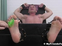 Hunky dude has his feet and body tickled while tied up